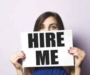 """Woman holding """"Hire Me"""" sign in front of her face"""